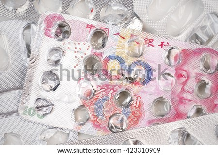 Banknote 100 Chinese yuan on an empty blister pack of tablets - stock photo