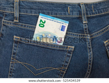 Banknote 20 euro sticking out of the back jeans pocket. Money for travel and shopping