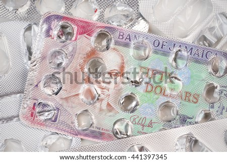 Banknote 50 Jamaican dollars on an empty blister pack of tablets - stock photo