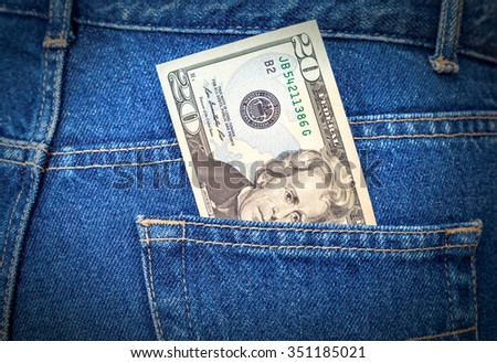 Banknote of twenty dollars sticking out of the blue jeans pocket - stock photo