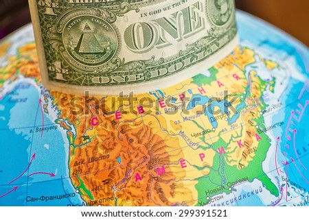 Banknote one dollar is worth on the globe from above - stock photo