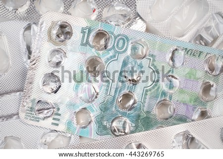Banknote 1000 Russian rubles on an empty blister pack of tablets - stock photo
