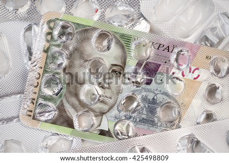 Banknote 500 Ukrainian hryvnia on an empty blister pack of tablets - stock photo