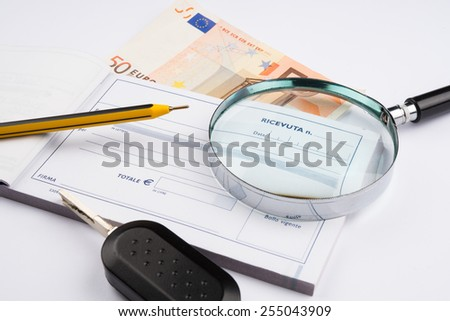 banknote with receipt and magnifying glass - stock photo