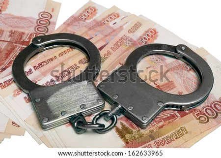 Banknotes and metal handcuffs - stock photo