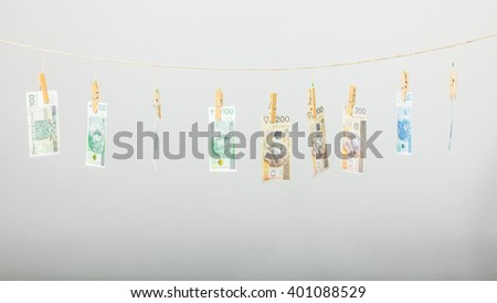 Banknotes cash money hang on laundry line on gray grey background. - stock photo