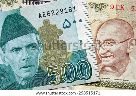 Banknotes from Pakistan and India showing heroes of the two nations: Jinnah and Gandhi.  Used banknotes, photographed at an angle with less than 80% of note showing. - stock photo
