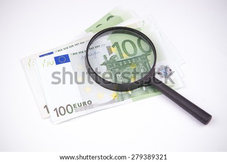 Banknotes hundred euros on a white background. Inspected with a magnifying glass - stock photo