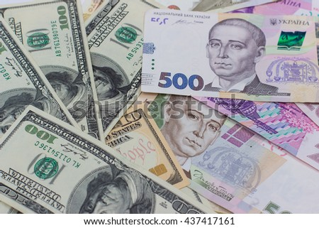 banknotes, image of dollars and new bills Ukrainian national currency hryvnia. namely hundred and five hundred hryvnia - stock photo