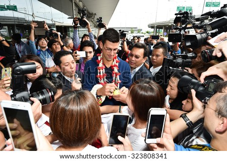 BANKOK THAILAND OCTOBER 01:Serbia's Novak Djokovic signs autographs for fans as he arrives in the lead up to The exhibition tennis match at suvarnabhumi airport  on Oct 1, 2015 in Thailand.  - stock photo