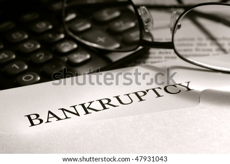 Bankruptcy filing legal notice letter with glasses and calculator (fictitious document with authentic legal language)