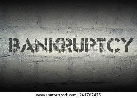 bankruptcy stencil print on the grunge white brick wall - stock photo