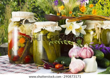 Banks with pickled vegetables - cucumbers, tomatoes, zucchini, and all the ingredients for their salting and preservation-salt, sugar, allspice, pepper, chili hot pepper, bay leaf, spices, dill,garlic - stock photo