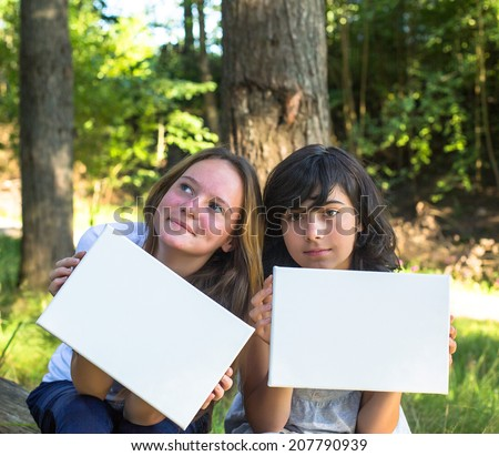 Banner for your message: Two young lovely girl holding clean white sheet paper, in the park. - stock photo