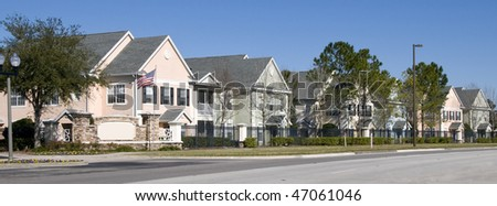 Banner image of Colorful fenced in row houses with blue sky - stock photo