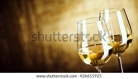 Banner of Two glasses of white wine standing side by side in a close up view over a panoramic abstract brown background with copy space