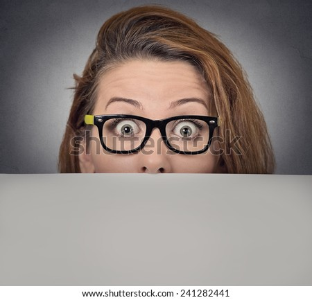 Banner sign woman peeking over edge of blank empty paper billboard. Beautiful young woman with glasses looking surprised and scared funny with wide open eyes isolated on grey wall background - stock photo
