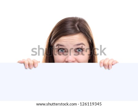 Banner sign woman peeking over edge of blank empty paper billboard with copy space for text. Beautiful woman looking surprised and scared - funny. Isolated on white background.