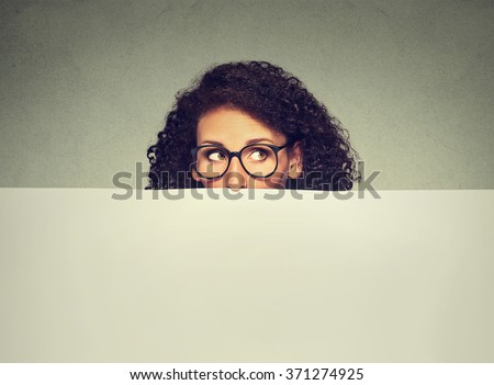 Banner sign woman peeking over edge of blank empty paper billboard with copy space for text. Beautiful woman in glasses looking surprised curious and scared funny. Isolated on gray wall background. - stock photo