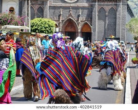 BANOS, ECUADOR - MARCH 4, 2014: Masked man in a striped poncho dances in a parade - stock photo