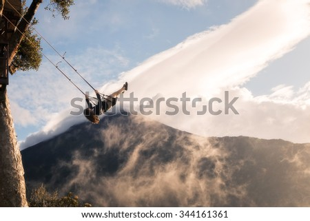 Banos, Ecuador - November 25, 2015: Young Girl Taking A Ride On The High Flying Rope Swing Hangs From A Tree House Called Casa Del Arbol, South America