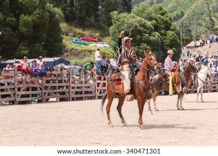 Banos, Ecuador - 30 November 2014: Young Indigenous Cowboy Riding A Horse And Throwing A Lasso, South America In Banos On November 30, 2014 - stock photo