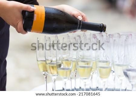 Banquet event. Waiter pouring champagne into glass.  - stock photo
