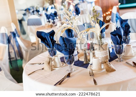Banquet hall decorated for wedding in white and blue.