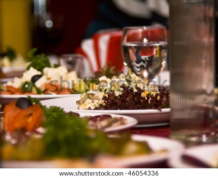 Banquet in the restaurant. Focus on one dish (shallow DOF) - stock photo