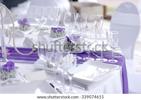 Banquet table decorated with flowers, napkins, glasses - stock photo