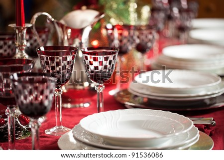 Banquet with red table setting. Red tablecloth, white dishes, silver cutlery and red checked goblet glasses plus some decorations