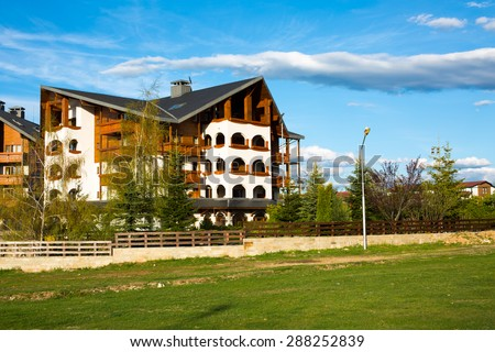 Bansko, Bulgaria - May, 3, 2015: Alpine stile wooden chalet of Kempinski Hotel, green meadow and cloudy blue sky in spring, Bansko, Bulgaria