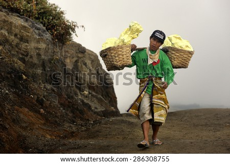 BANYUWANGI,INDONESIA - May 26,2015 : After extraction of sulfur from Kawah Ijen volcanic crater lake ,workers carry basket full of sulfur on their shoulder and unload the baskets 3,5 Km away. - stock photo
