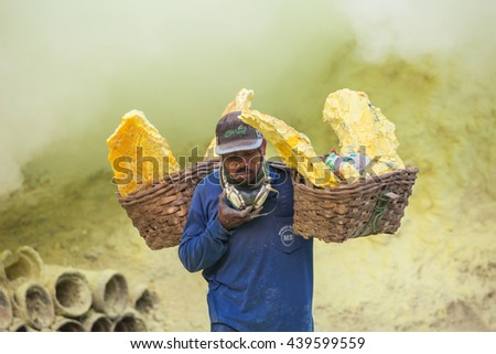 BANYUWANGI, INDONESIA - OCTOBER 27, 2014: Unidentified Sulfur miner inside crater of Ijen volcano, East Java, Indonesia. - stock photo