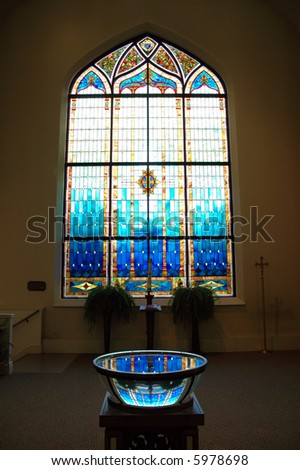 baptism bowl reflection off of stained glass in a church