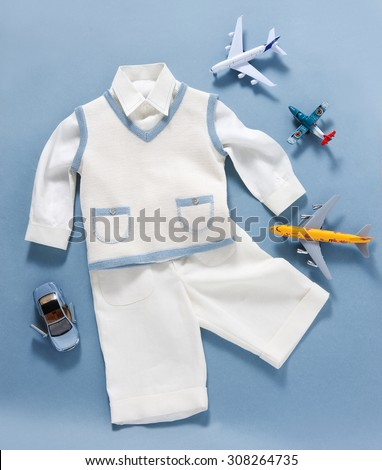 baptism boy clothes in plan with toys on a blue background - stock photo