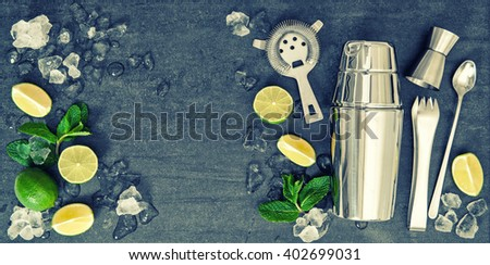 Bar accessories and ingredients for cocktail drink lime, mint, ice. Vintage style toned picture - stock photo