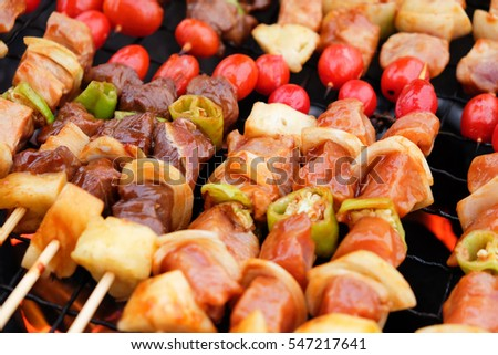 Bar-B-Q grill of meat and veggies, Coal grill of pork skewers with tomatoes, onion and peppers. barbecue camping dinner.