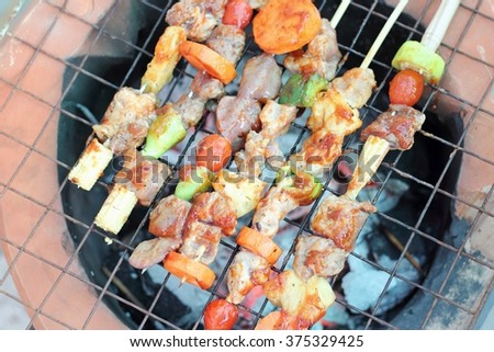 Bar-B-Q or BBQ. Coal grill of chicken meat skewers with tomatoes and peppers. Barbecuing dinner. - stock photo