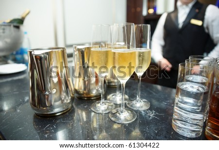 Bar counter with champagne, bartender in background - stock photo