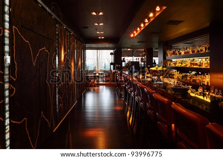 bar counter with red tall chairs in empty comfortable restaurant; lot of drinks on shelves - stock photo