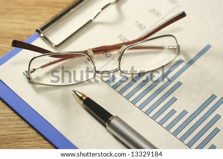 Bar graph on a blue clipboard with a pen and glasses on a desk. - stock photo