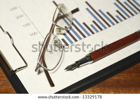 Bar graph on a clipboard with a pen and glasses on a desk. - stock photo