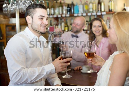 Bar happy visitors waiting for table and drinking wine at tavern. Focus on the man - stock photo