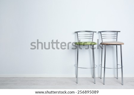 Bar high chairs on white wall background - stock photo