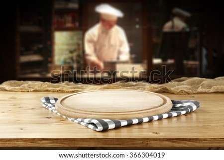bar interior with chef of kitchen and free space on yellow board and shabby table  - stock photo