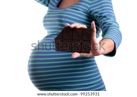Bar of chocolate in pregnant woman hand - stock photo