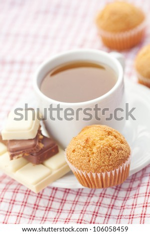 bar of chocolate,tea and muffin on plaid fabric - stock photo