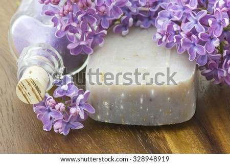bar of natural soap, bath salt and lilac flowers - stock photo