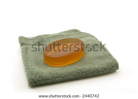 bar of soap and a face cloth on white background - stock photo